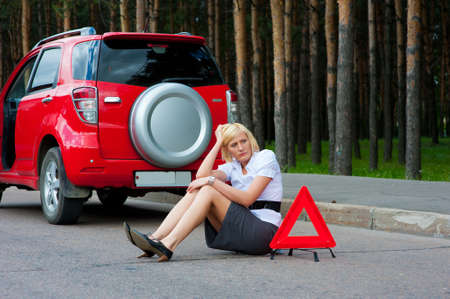 road assistance: Blonde girl helplessly sitting on the road waiting for car service
