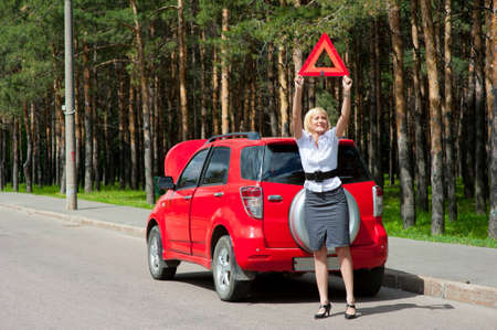 Blonde girl asks for help on the road near her broken car Stock Photo - 9954960
