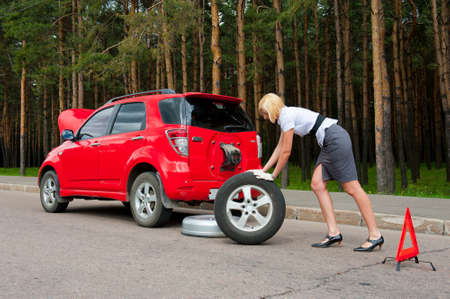Blonde changing tire on a road Stock Photo - 9954993