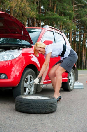 Blonde changing tire on a road photo