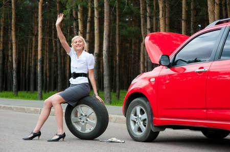 broken car: Chica rubia pide ayuda en la carretera cerca de su coche rota