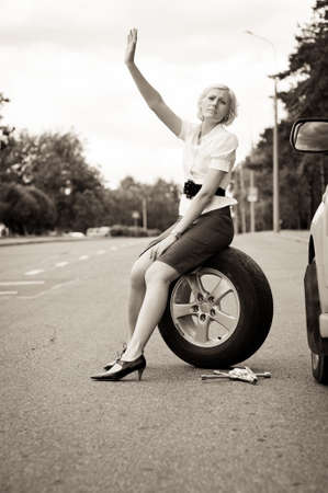 Blonde girl asks for help on the road near her broken car. Toned image Stock Photo - 9956208