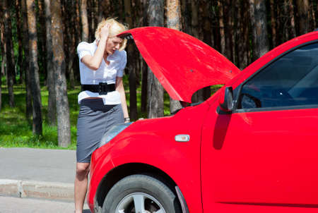 Blonde girl looks under the hood of a broken car Stock Photo - 9955118