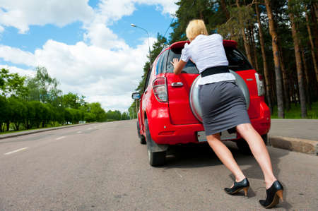 Blonde girl pushes her broken car to the car service Stock Photo