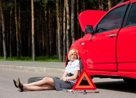 Blonde girl sitting near broken car and waiting for help