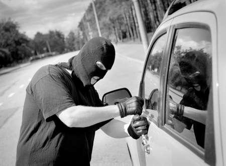 car theft: Ladr�n se rompe en una puerta de autom�vil en la calle