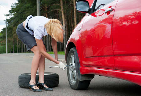 Blonde changing tire alone on a road photo
