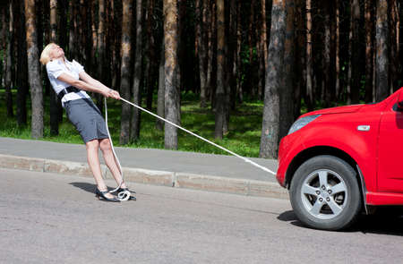 Blond meisje trekt een kapotte auto met een touw Stockfoto