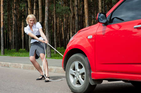 Blonde girl pulls a broken car with a rope Stock Photo - 10065421