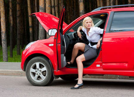 one adult only: Blonde girl sitting in broken car and waiting for help Stock Photo