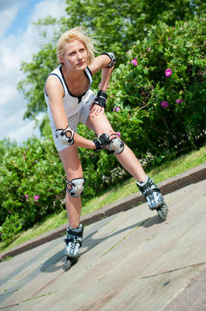 Girl roller-skating in the park at summer photo
