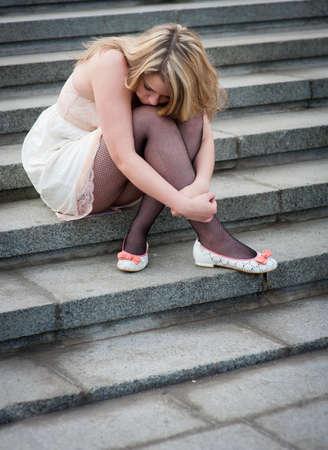 Sad lonely girl sitting on the steps Stock Photo - 10065415