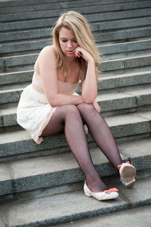 Sad lonely girl sitting on the steps Stock Photo - 10065414