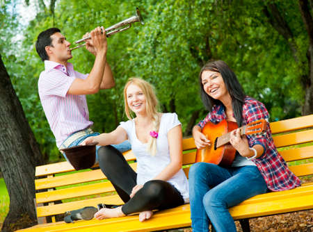 Young friends play the guitar and trumpet in the park photo