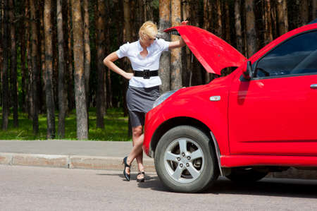 Blonde woman looks under the hood of a broken car Stock Photo