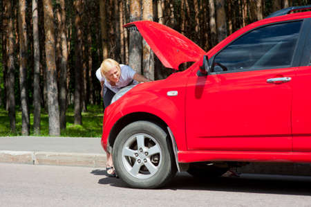 Blonde woman tries to repair her broken car photo