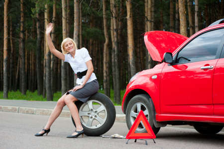 road assistance: Blonde girl asks for help on the road near her broken car