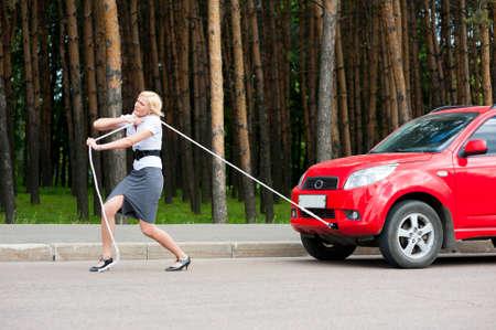 Blonde Mädchen zieht ein kaputtes Auto mit einem Seil