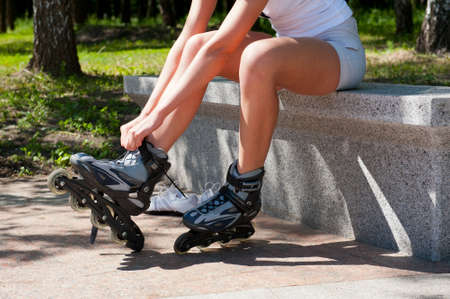rollerblading: Young woman put on rollers for roller-skating in the park