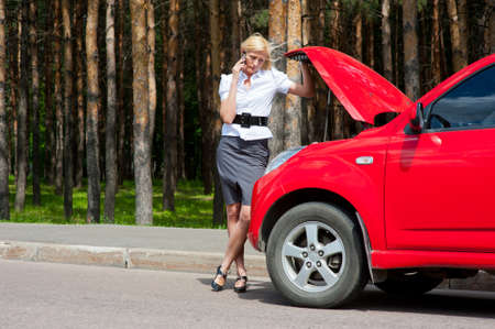 Blonde woman calls to car service on a road photo