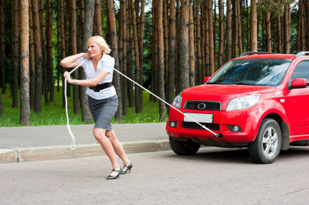 Blonde girl pulls a broken car with a rope photo