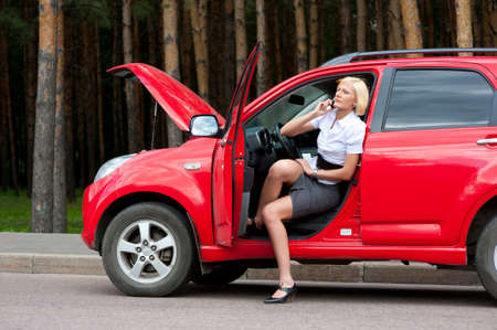 Blonde woman calls to car service on a road