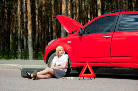 Blonde girl helplessly sitting on the road waiting for car service photo