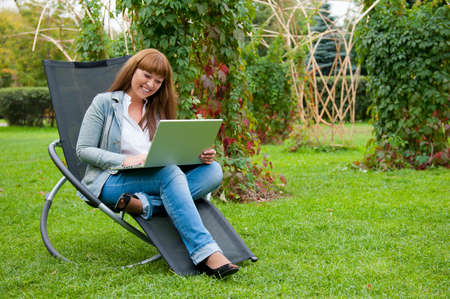 Young woman working on laptop in the park