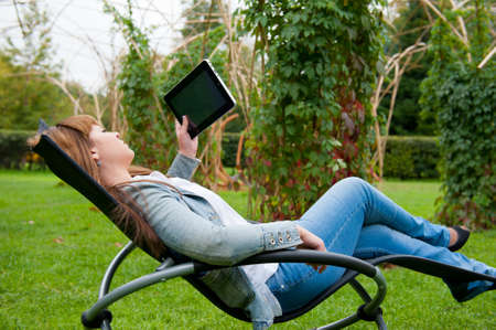 person outside: Young woman reading in tablet pc in the park