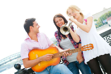 Young friends play the guitar and trumpet on the embankment photo