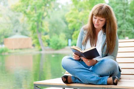persona sentada: Joven leyendo un libro sentado en el banquillo en el Parque
