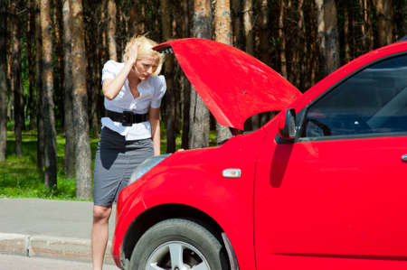 Blonde woman looks under the hood of a broken car photo
