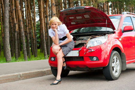 Blonde girl helplessly sitting waiting for car service photo
