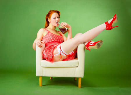 Pin-up style girl sitting on the chair and drinks whiskey Stock Photo