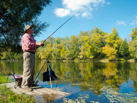 fishing tackle: Senior fisherman catches a fish in the river at the bait