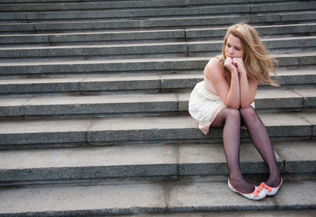 Sad lonely girl sitting on the steps photo