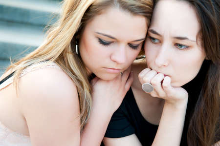 Two sad young beautiful girls portrait outdoors photo