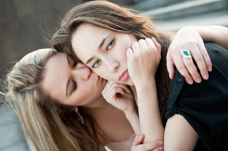 lesbians: Two sad girls sorry for each other outdoors Stock Photo