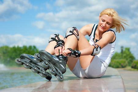 corrects: Blonde girl corrects the clasp of roller skates Stock Photo