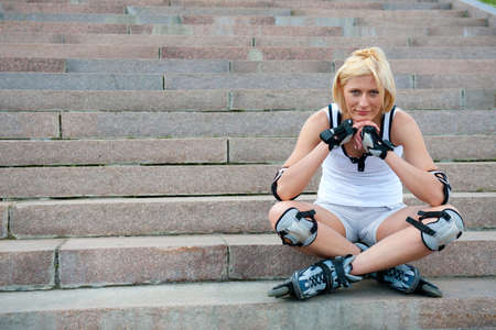 Young woman in roller skates sitting on the stairs Stock Photo - 10841733