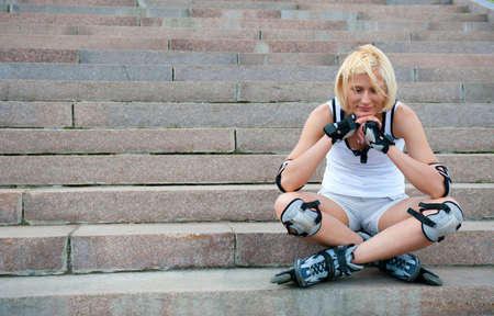 Young woman in roller skates sitting on the stairs photo