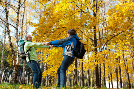 Happy young couple with backpacks having fun in the park. Fall. Stock Photo - 10992148