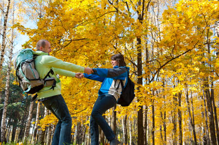 Happy young couple with backpacks having fun in the park. Fall.