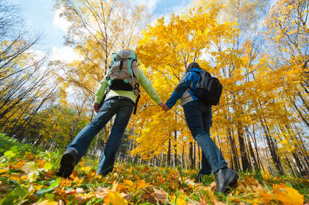 trek: Young couple with backpacks in the park. Fall. Stock Photo