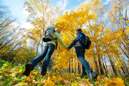 Happy young couple with backpacks in the park. Fall.