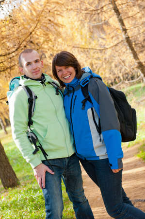 Happy young couple with backpacks in the park. Fall. Stock Photo - 10992120