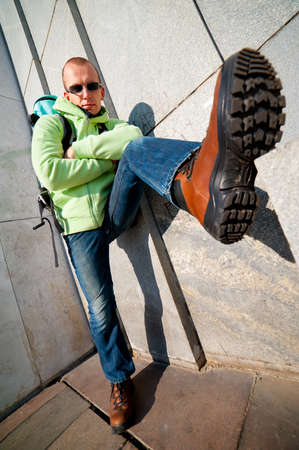 Wide angle urban portrait of a stylish man in hiking boots photo