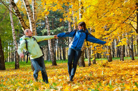 Happy young couple with backpacks in the park. Fall. photo