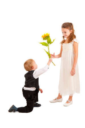 Boy gives girl a yellow flower isolated photo