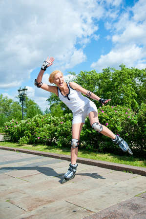Girl roller-skating in the park, she is still studying, and nearly falls photo